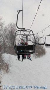 スキー場のリフトに乗る子供達